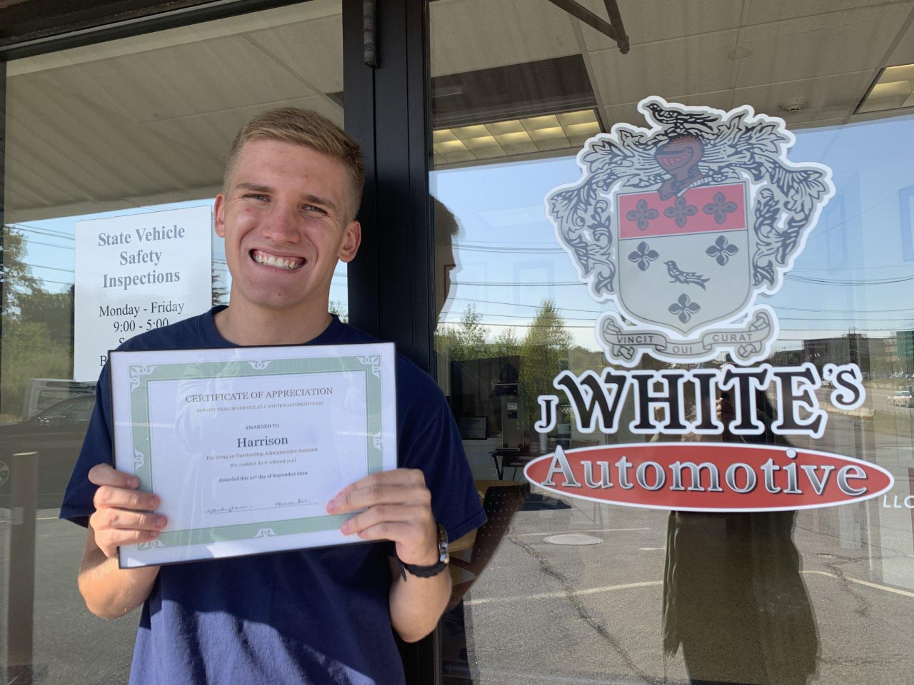 Harrison Shaffer proudly showing off his 1 year of employment certificate from J. White's Automotive.